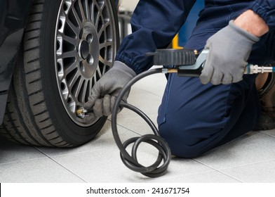 Closeup Of Mechanic At Repair Service Station Checking Tyre Pressure With Gauge