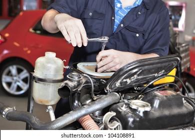 Close-up of mechanic repairing an engine in garage.