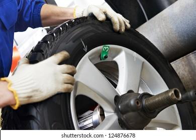 Close-up of mechanic repairman hands during balancing automobile car wheel on balancer