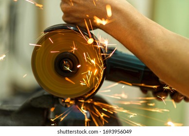 Close-up of a mechanic working as a grinder, sparks fly. Bicycle workshop. Repairs.