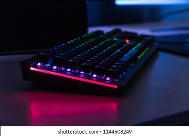 Close-up of a mechanical RGB gaming keyboard lit at night