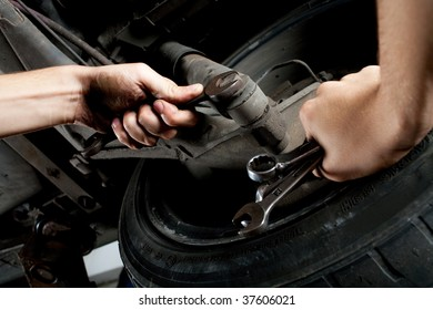 closeup of mechanics hands working below car with wrench