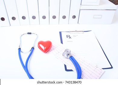 Closeup of medical stethoscope on a rx prescription, red heart isolated on white background