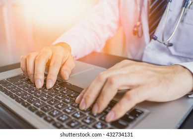 Close-up of a medical worker typing on laptop.