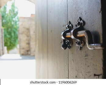 Closeup of medieval deadbolt on brown wooden door with outdoor courtyard in background