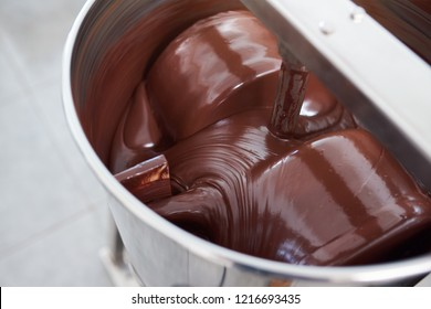 Closeup of melted chocolate being turned in a large stainless steel mixing machine in an artisanal chocolate making factory