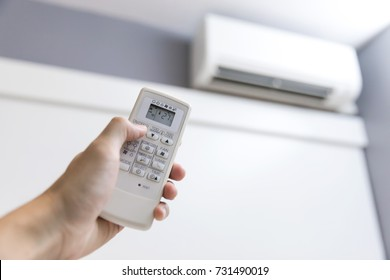 Close-up of men hand operating air conditioner with remote control