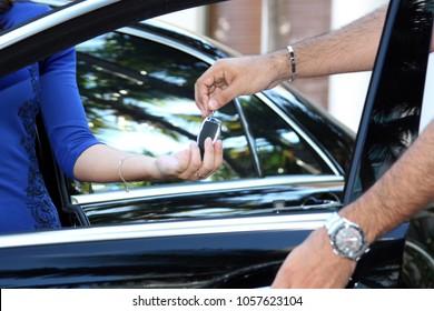 Closeup of men handling car keys to a woman
