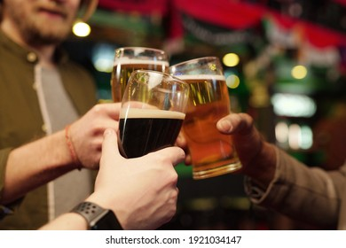 Close-up of men holding glasses of beer and toasting during their meeting in the bar