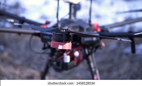 Close-up of men prepared quadcopter for flight. Clip. Two men admire latest version of quadcopter with powerful motors and professional camera for photography from air