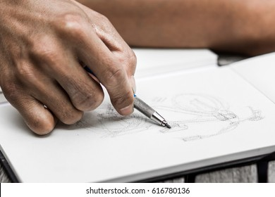 closeup of men's hand with pencil drawing on notepad