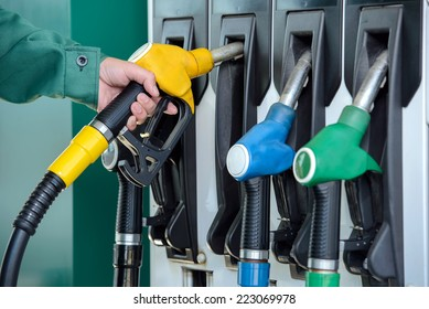 Close-up of a men's hand using a fuel nozzle at a gas station. Petrol station. Filling station. Petrol. Gasoline.