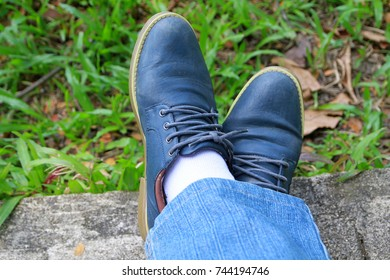 Close-up of men's leather shoes while relaxing on a natural background with blue jeans.