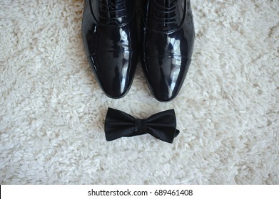 Close-up of men's shoes and a bow tie. All in black.