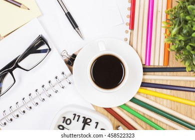 Closeup of messy workspace with coffee cup, glasses, clock, plant, colorful pencils and other stationery items