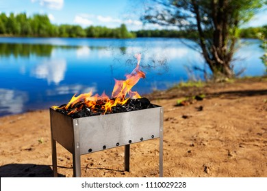 Closeup metal brazier with fire at sunny summer river background. Concept of camping and travelling.