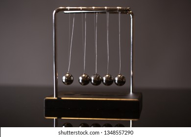Closeup metal Newton cradle placed on gray background as representation of momentum concept