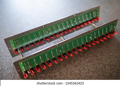 Close-up of a metal panel with microchips connected to each other with red wires in the manufacture of electronic equipment. The concept of complex technical equipment at the factory