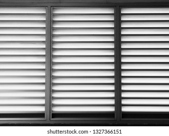 Closeup of metal sheet louver or slats on the wall for ventilation and allowing light to pass through. Indoor interior, decoration and background in black and white. Metal structure and architecture.