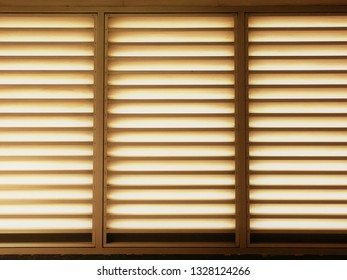 Closeup of metal sheet louver or slats on the wall for ventilation and allowing light to pass through. Indoor interior, decoration and background in warm sepia tone. Metal structure and architecture.
