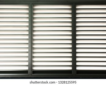 Closeup of metal sheet louver or slats on the wall for ventilation and allowing light to pass through. Indoor interior, decoration and background in dark grey tone. Metal structure and architecture.