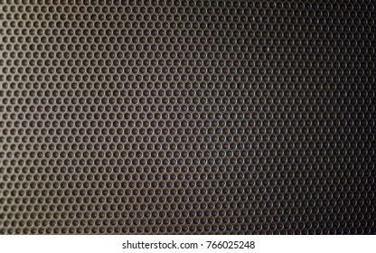 Closeup of a metal soundbox. Focus in the middle and the outer parts are blurry. Light effects are part of the shot.