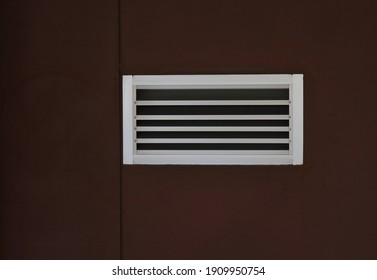 Closeup metal vent grille on rough brown wall