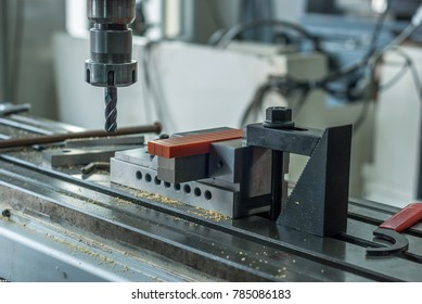 Closeup of a metal work piece in a milling machine drilling metal modern processing technology