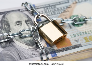 Closeup of metallic chain and padlock around dollar bundle