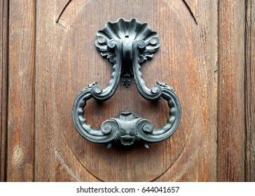 Closeup of metallic door knocker on wooden door in Florence, Italy.