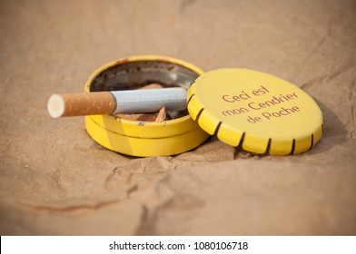 "closeup of metallic pocket ashtray with texte in french on brown background ""this is my pocket ashtray"" (ceci est mon cendrier de poche)"