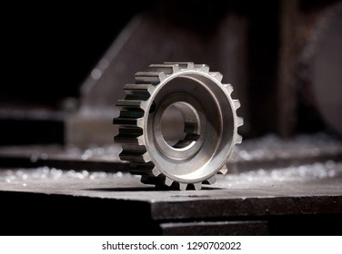 closeup of metallic shiny cogwheel - mechanic steel detail on industrial background