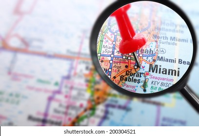 Closeup of Miami map with red push pin and magnifying glass