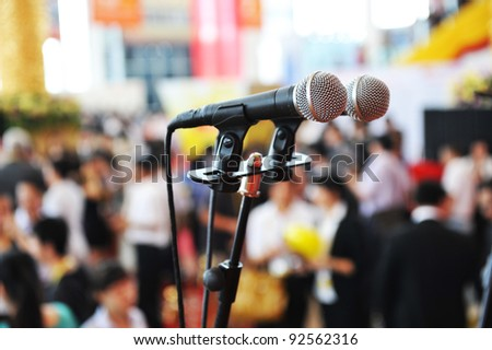 Closeup microphone in auditorium with people.