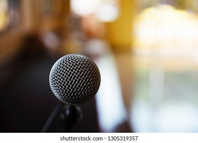 Closeup of microphone with blurred auditorium background.
