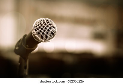 Close-up of microphone in conference seminar for speech with people meeting room in event blur light background