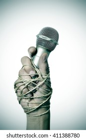 closeup of a microphone in the hand of a young man tied with rope, depicting the idea of the repression of the mass media or the lack of the freedom of speech