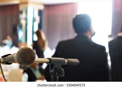 Close-up of the microphone on the table with a light brown tablecloth on the stage in front of the room, with a blur of people sitting down below.
