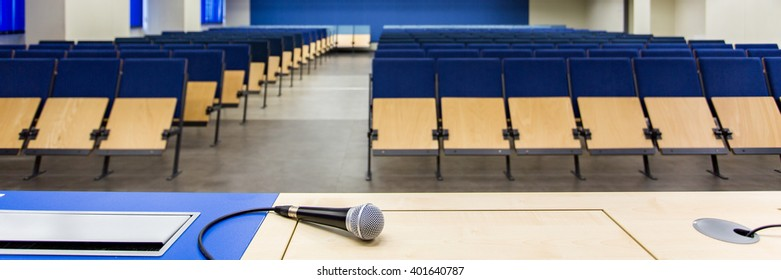 Close-up of microphone on a wooden desk in lecture hall with blue chairs