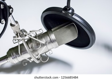 Closeup of a Microphone and Recording Equipment in a Podcast Studio on a White Background, Horizontal Orientation