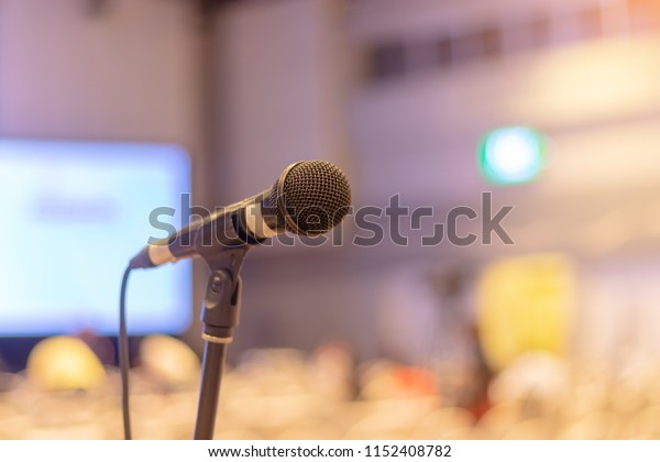 Close-up of microphone in seminar room or conference hall light for speaking or talking for lecture. Meeting Conference Training Learning Concept. Blurred background and soft - focus.