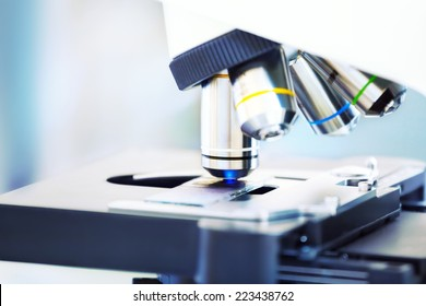 Closeup of microscope with blood sample background.