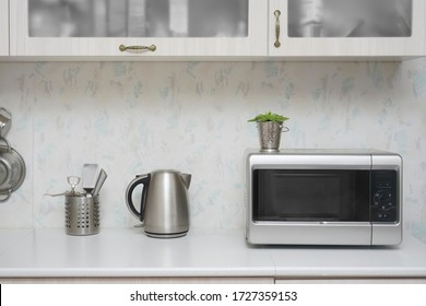 Close-up microwave and stainless electric kettle. white modern wooden table in the kitchen. plate with many fruits - oranges. gray table with kitchen background. no people