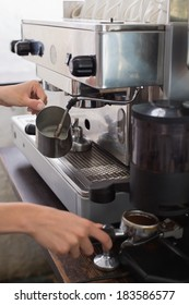 Close-up mid section of a barista prepares espresso in coffee shop