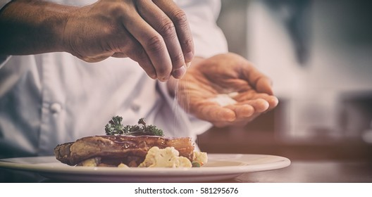 Closeup mid section of a chef putting salt in the kitchen