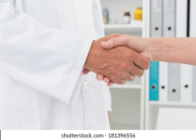 Close-up mid section of a doctor shaking hands with patient at medical office
