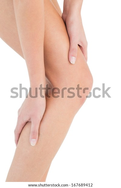 Close-up mid section of a fit young woman with leg pain over white background