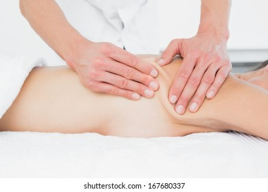 Close-up mid section of a male physiotherapist massaging woman's body in the medical office