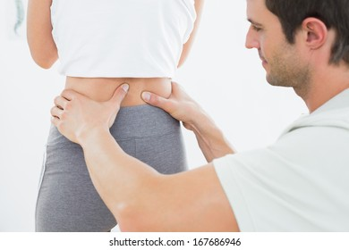 Close-up mid section of a physiotherapist examining woman's back in the medical office