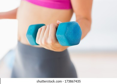 Closeup mid section of a young woman lifting dumbbell weight in a bright gym